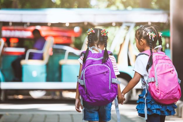 Asiatischer schüler scherzt mit dem rucksack, der hand hält und zusammen mit schulbus zur schule geht Premium Fotos