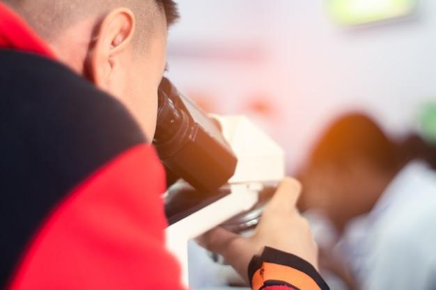 Asiatischer student, der mikroskop in der wissenschafts-klasse schaut Premium Fotos