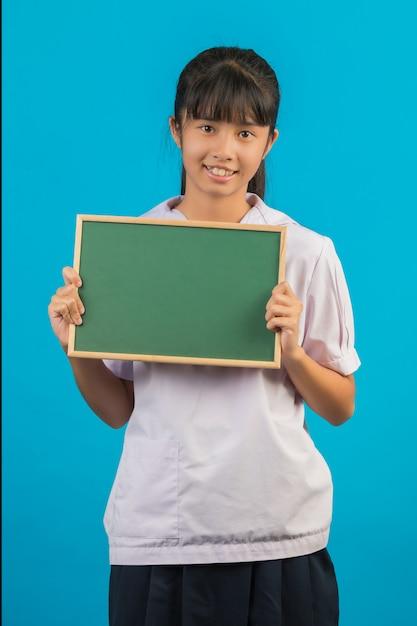 Asiatischer student mit dem langen haarmädchen, das ein grünes brett auf einem blau hält. Kostenlose Fotos