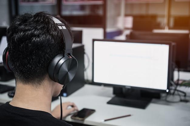 Asiatischer student young-mann-tragendes kopfhörerhören Premium Fotos