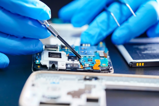 Asiatischer techniker, der mikroschaltungshauptplatine von smartphone repariert. Premium Fotos