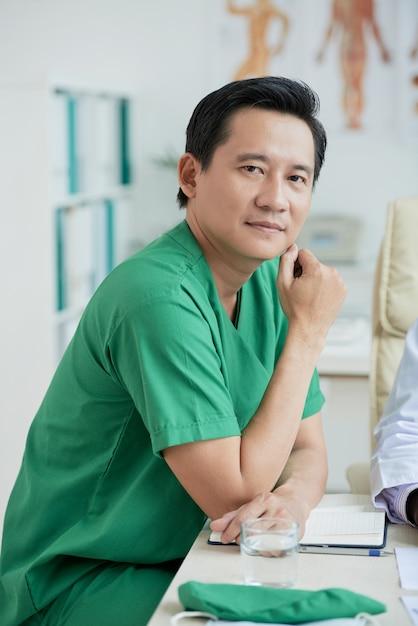 Asiatischer therapeut wearing green uniform sitting am schreibtisch, der kamera-porträt betrachtet Kostenlose Fotos