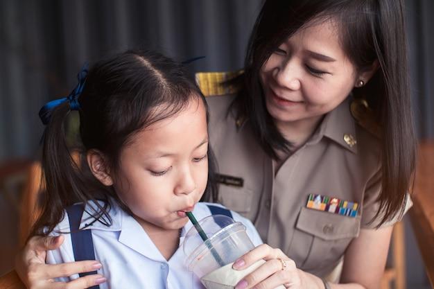 Asiatischer tochtergetränksaft durch rohr von glassa mit ihrer mutter. Premium Fotos