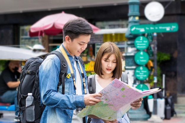 Asiatischer touristischer wanderer der jungen paare, der nach richtung auf die karte sucht Premium Fotos