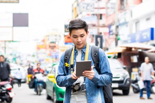 Asiatischer touristischer wanderer, der tablette beim reisen in straße thailand khao san verwendet Premium Fotos