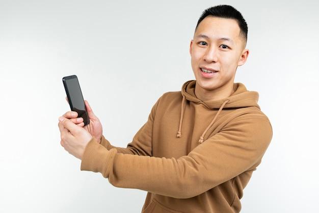 Asiatischer typ zeigt ein smartphone in seiner hand auf einem weiß Premium Fotos