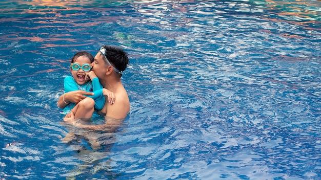 Asiatischer vater, der mit seiner tochter im swimmingpool küsst und spielt Premium Fotos