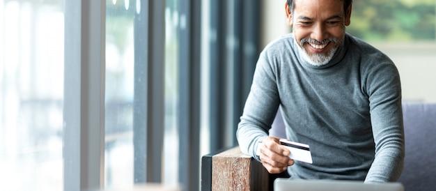 Asiatischer vater des attraktiven bärtigen hippies oder hispanischer alter mann, der laptop- und kreditkartenzahlung verwendet Premium Fotos