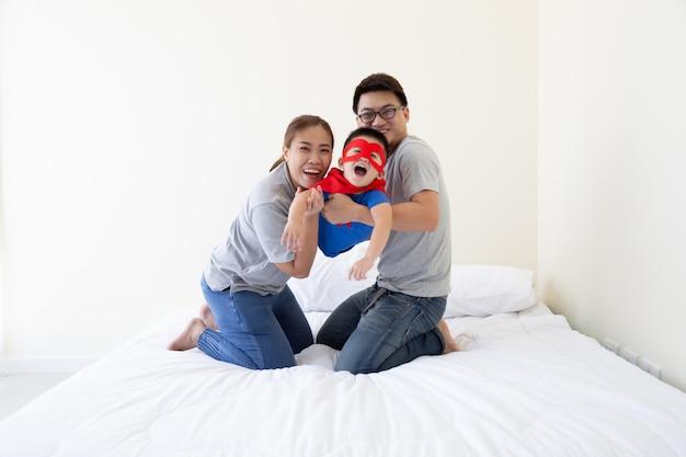 Asiatischer vater, mutter und sohn spielen superhelden auf dem bett im schlafzimmer. freundliche familie, die spaß hat Premium Fotos