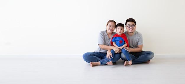 Asiatischer vater, mutter und sohn spielen superhelden auf dem boden im raum. glücklicher familientag Premium Fotos