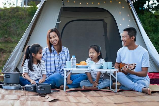 Asiatischer vater, mutter und zwei kindermädchen, die spaß haben, außerhalb des zeltes auf dem campingplatz in der schönen natur zu picknicken. Premium Fotos