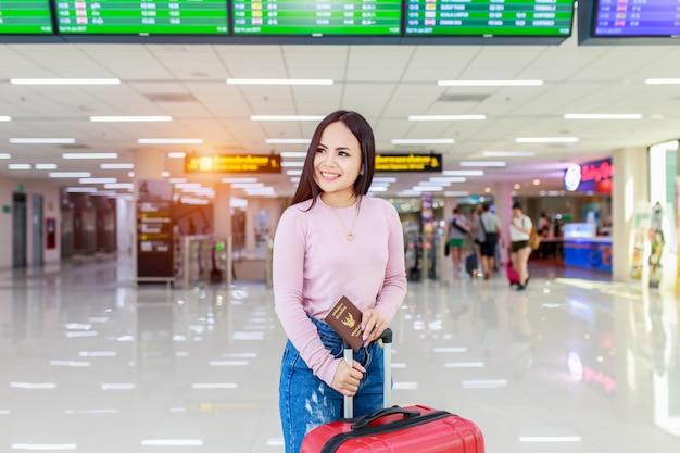 Asiatischer weiblicher reisender, der flugabflugbrett überprüft. Premium Fotos