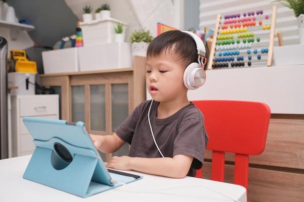 Asiatisches 4 jahre altes kleinkindjungenkind, das tablet-pc-computer, fernunterricht, aktivitäten für kindergartenkonzept verwendet Premium Fotos