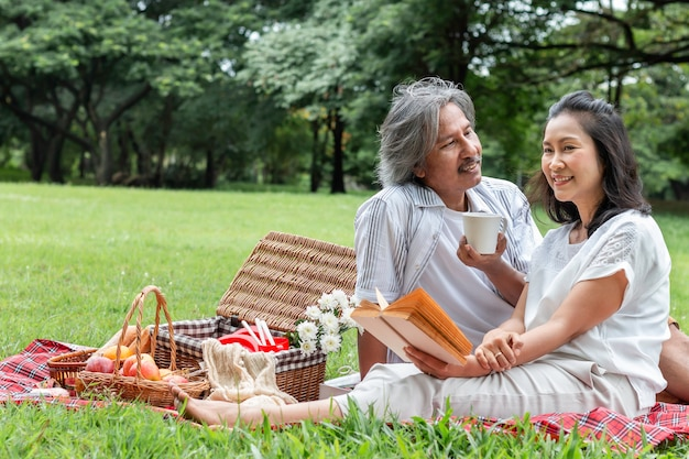 Asiatisches älteres paarlesebuch und -picknick am park. Premium Fotos