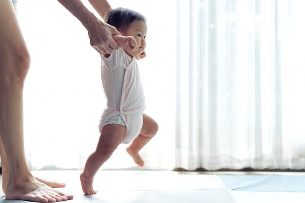 Asiatisches baby, das erste schritte unternimmt, gehen vorwärts auf die weiche matte Premium Fotos