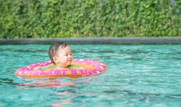 Asiatisches baby der nahaufnahme sitzen in einem boot für kinder im swimmingpoolhintergrund mit lächelngesicht im glücklichen gefühl Premium Fotos