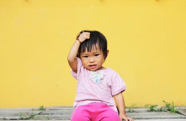 Asiatisches babykindermädchen setzte ihre hand auf ihren kopf. Premium Fotos