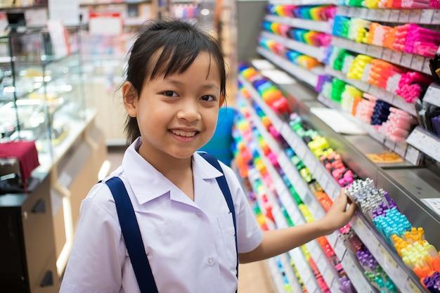 Asiatisches einheitliches studentenmädchen in kaufenden stiften und im schulbedarf des briefpapierladens Premium Fotos