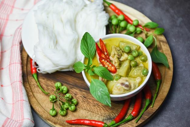 Asiatisches essen auf dem tisch. grünes curry-huhn des thailändischen essens auf suppenschüssel und thailändischen reisnudeln fadennudeln mit zutat kräutergemüse Premium Fotos