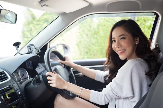 Asiatisches frauenautofahren und lächeln glücklich mit frohem positivem ausdruck Premium Fotos