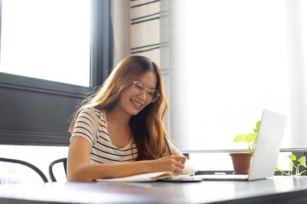 Asiatisches geschäftsmädchen fangen an, mit laptop-computer am café zu arbeiten Premium Fotos