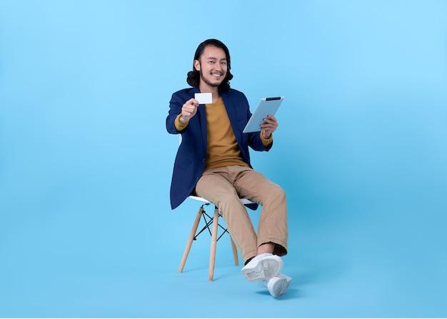 Asiatisches glückliches lächeln des geschäftsmannes, das kreditkarte zeigt und eine digitale tablette verwendet, während auf stuhl auf hellem blau sitzt. Kostenlose Fotos