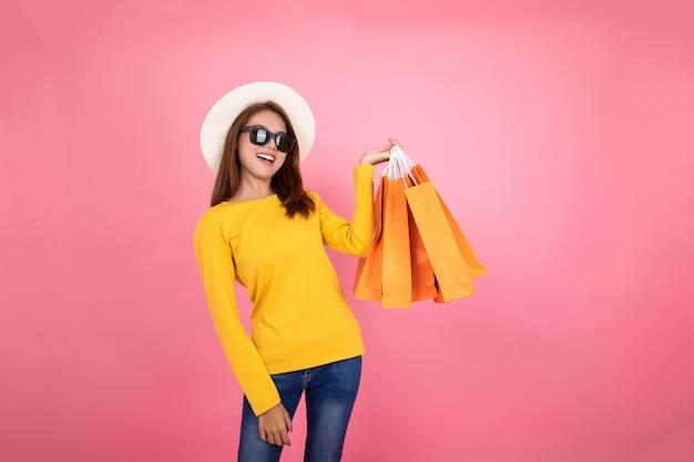 Asiatisches hübsches mädchen, welches die kaufenden orange taschen schauen weg auf rosa hintergrund, buntes einkaufskonzept hält. Premium Fotos