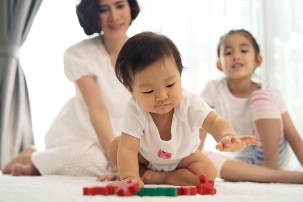 Asiatisches junges baby, das zu hause hölzerne spielwaren mit unterstützung von ihrer schwester und von mutter spielt. Premium Fotos