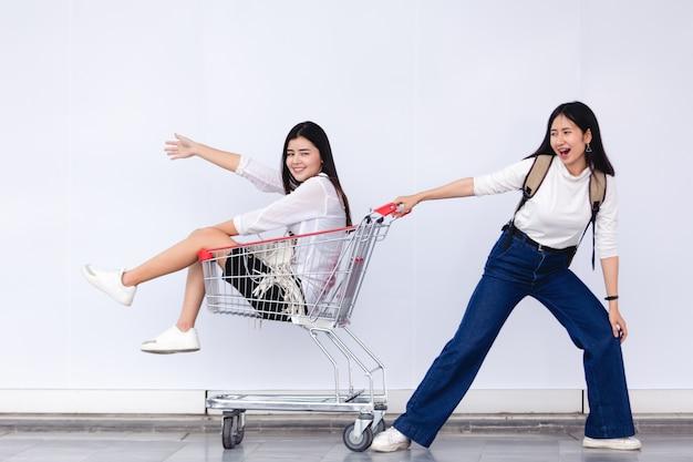 Asiatisches junges mädchen, das im warenkorb für marketing-konzept sitzt Premium Fotos