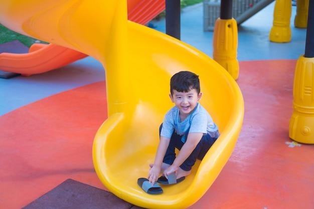 Asiatisches kind, das dia am spielplatz unter dem sonnenlicht im sommer spielt Premium Fotos