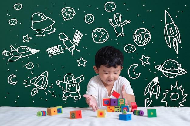 Asiatisches kind, das lernt, indem es mit seiner fantasie über wissenschaft und weltraumabenteuer spielt Premium Fotos