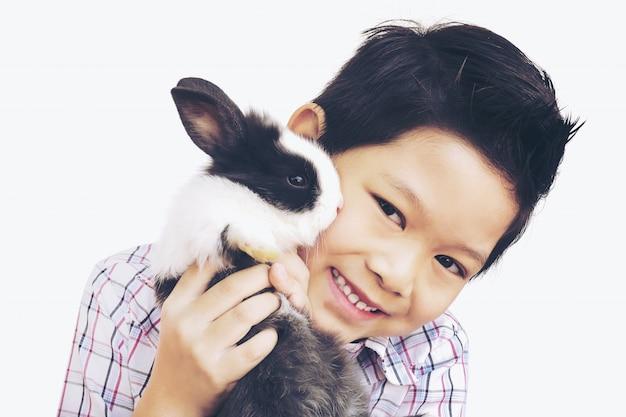 Asiatisches kind, das mit dem reizenden babykaninchen lokalisiert über weiß spielt Kostenlose Fotos
