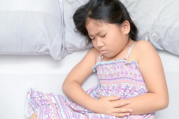 Asiatisches kind, das unter magenschmerzen leidet Premium Fotos