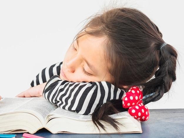 Asiatisches kind schläft beim lesen eines großen buches Kostenlose Fotos