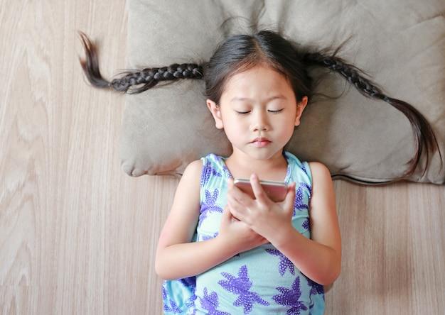 Asiatisches kindermädchen, das den smartphone liegt auf bretterboden schaut. draufsicht Premium Fotos