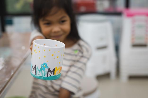 Asiatisches kindermädchen, das ihre eigene arbeit nach fertiger farbe auf keramikglas mit ölfarbe zeigt. kreative aktivitätsklasse für kinder in der schule. Premium Fotos
