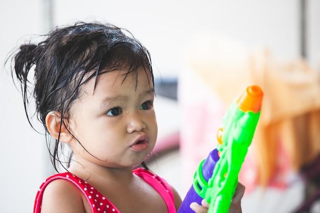 Asiatisches kindermädchen, das spaß hat, wasser mit wasserwerfer in songkran-festival thailand zu spielen Premium Fotos