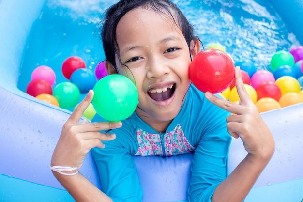 Asiatisches kindermädchen, das spaß im garten-planschbecken mit farbball hat Premium Fotos