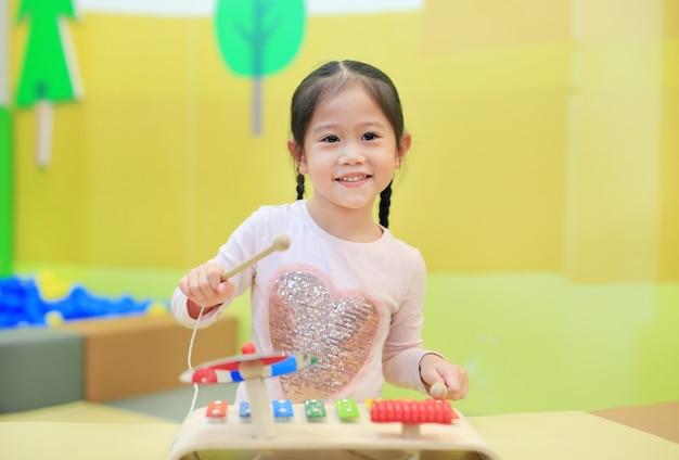 Asiatisches kindermädchen, das spaß mit spielwaren, musikinstrumente hat. Premium Fotos