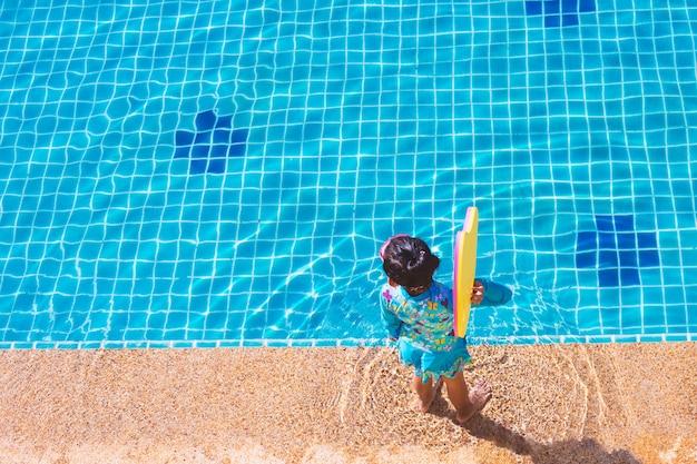 Asiatisches kindermädchen im badeanzug, der sich hin- und herbewegende schaumseite das pool steht und hält. Premium Fotos