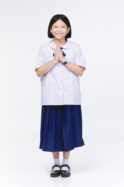 Asiatisches kindermädchen in der uniform des studenten, stellvertretender sawaddee gemeines hallo. Premium Fotos