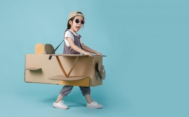 Asiatisches kleines kindermädchen, das mit pappspielzeugflugzeug spielt Premium Fotos