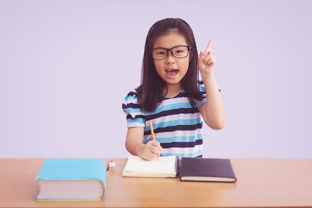 Asiatisches kleines mädchen, das ein buch auf tisch schreibt. zeigefinger oben mit offenem mund, isoliert auf grauem hintergrund Premium Fotos