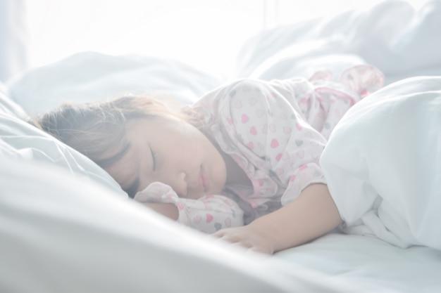 Asiatisches kleines mädchen, das im bett auf der morgenzeit mit sonnenaufganglichtweichzeichnung schläft Premium Fotos