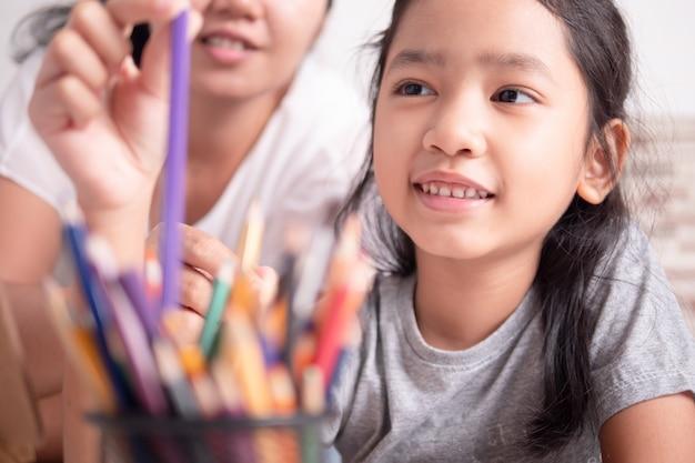 Asiatisches kleines mädchen und eine frau, die eine farbe für das malen vorwählt Premium Fotos