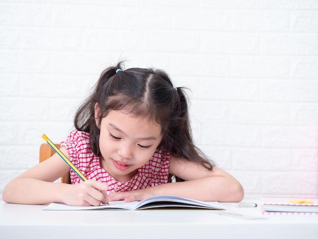 Asiatisches kleines süßes mädchen 6 jahre alt sitzend und schreibend an notiz auf weißem tisch. schönes kind der vorschule, das hausaufgaben zu hause schreibt. Premium Fotos