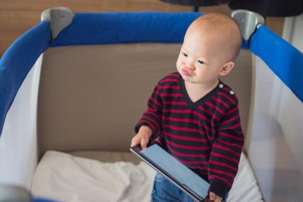 Asiatisches kleinkindbaby, das in der krippe steht und tablette hält Premium Fotos