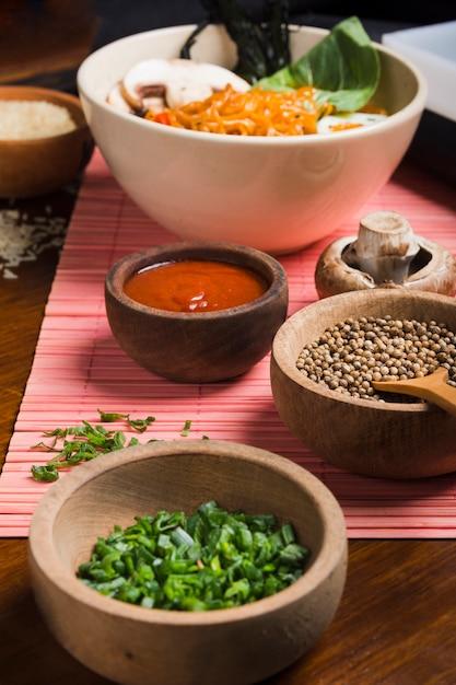 Asiatisches lebensmittel mit hölzerner schüssel frühlingszwiebel- und koriandersamen mit soße Kostenlose Fotos