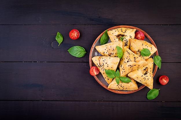 Asiatisches lebensmittel, samsa (samosa) mit hühnerleiste und grüne kräuter auf hölzerner, draufsicht Premium Fotos