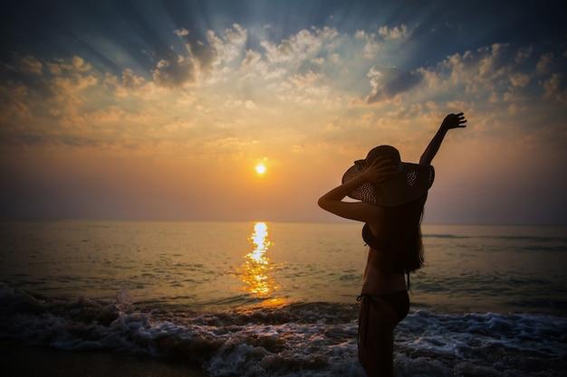 Asiatisches mädchen am strand, sie passt den sonnenuntergang auf. Premium Fotos